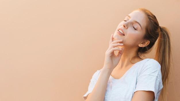 Mulher jovem bonita pensativa com olho fechado contra o pano de fundo bege Foto gratuita