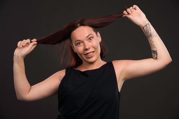 Mulher jovem brincando com os cabelos. Foto gratuita