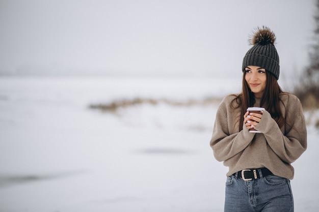 Mulher jovem, café bebendo, exterior, em, inverno, parque Foto gratuita