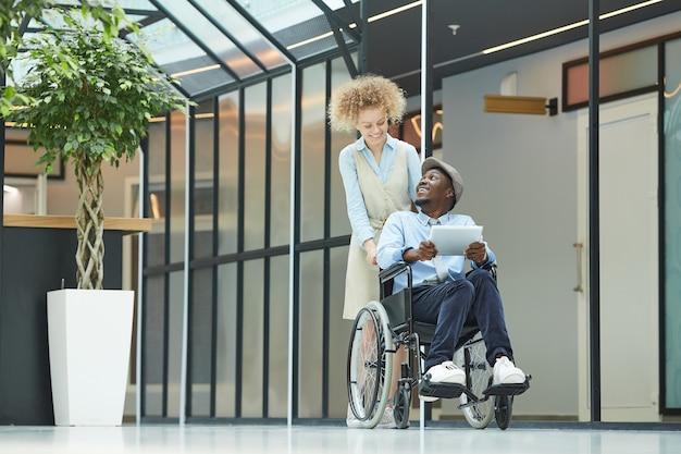 Mulher jovem caminhando pelo corredor com um homem deficiente em cadeira de rodas usando o tablet pc Foto Premium