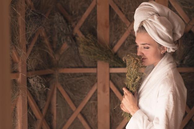 Mulher jovem, cheirando, erva, flores, ficar, em, a, sauna Foto gratuita