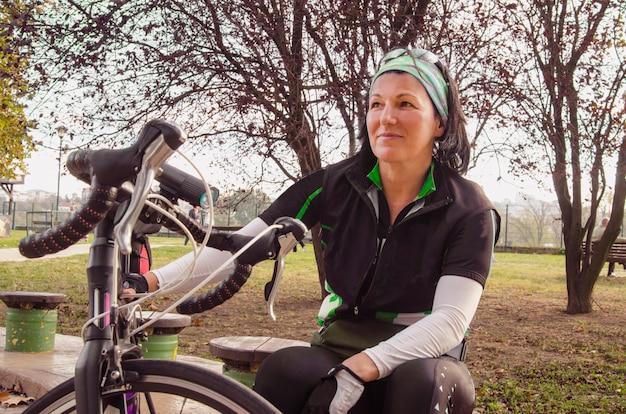 Mulher jovem ciclista descansando no parque. menina sentado e relaxando para viagem de passeio de bicicleta Foto Premium