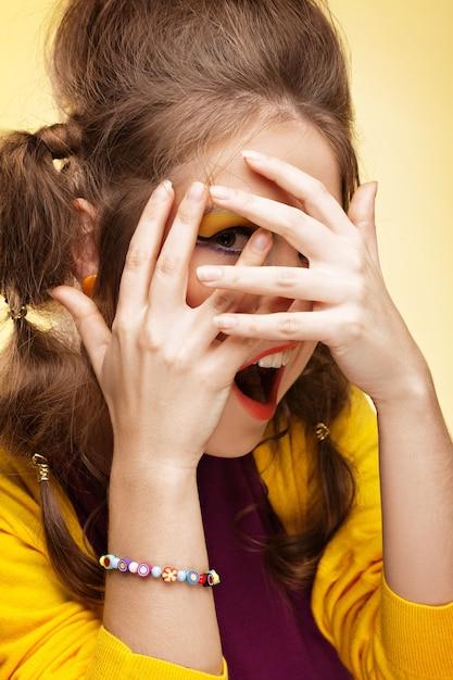 Mulher jovem cobrindo o rosto com as mãos e olhando por entre os dedos Foto Premium