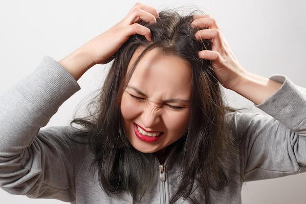 Mulher jovem coçando a cabeça com os dedos Foto Premium