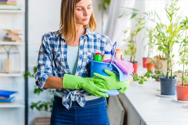 Mulher jovem, com, balde, de, limpeza, equipamentos Foto gratuita