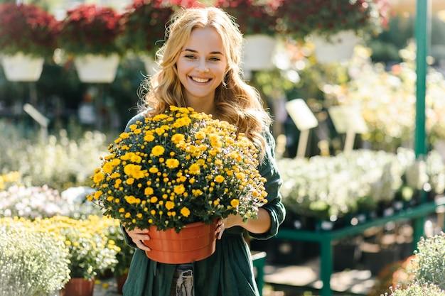 Mulher jovem com belos cabelos loiros e sorriso gentil, vestida com um manto verde com cinto está trabalhando em estufa Foto gratuita