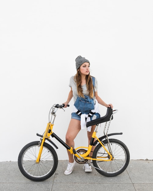 Mulher jovem, com, bicicleta, ficar, ligado, calçada Foto gratuita