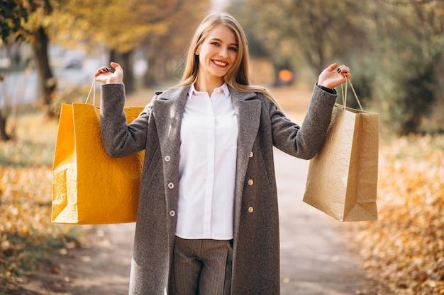 Mulher jovem, com, bolsas para compras, andar, parque Foto gratuita