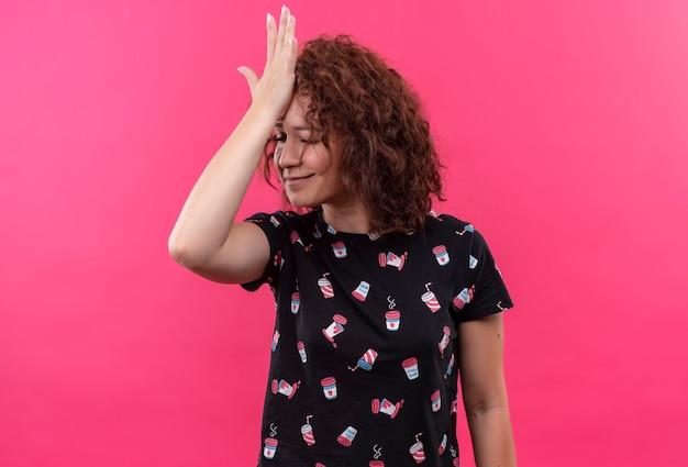Mulher jovem com cabelo curto e encaracolado em pé com a mão na cabeça por engano, esqueci, conceito de memória ruim em pé sobre a parede rosa Foto gratuita