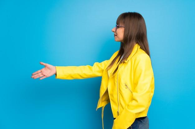 Mulher jovem, com, casaco amarelo, ligado, azul, fundo, handshaking, após, bom negócio Foto Premium