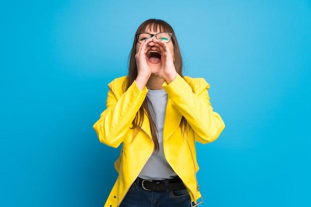 Mulher jovem, com, casaco amarelo, ligado, experiência azul, shouting, e, anunciando, algo Foto Premium