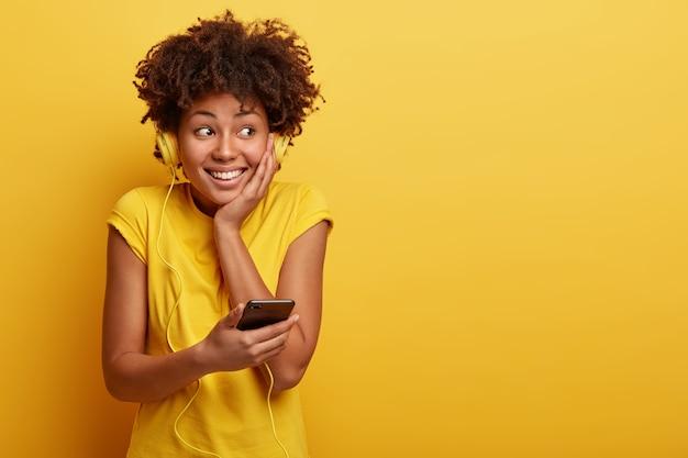 Mulher jovem com corte de cabelo afro e fones de ouvido amarelos Foto gratuita