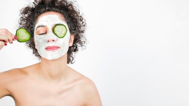 Mulher jovem, com, cosméticos, ligado, rosto, aplicando, pepino, para, dela, olho Foto gratuita