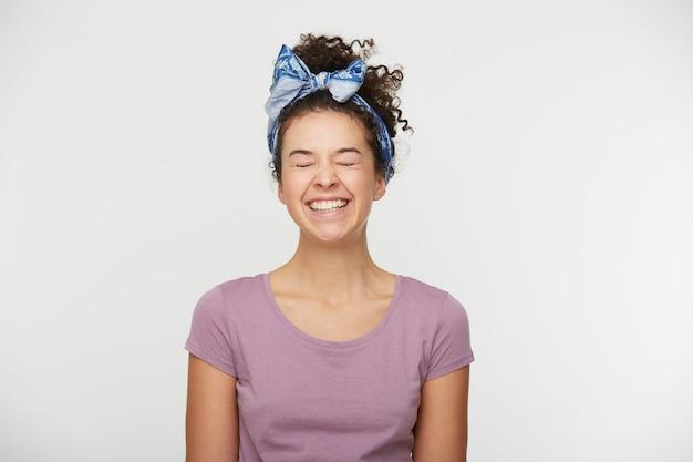 Mulher jovem com expressão positiva, vestida com camiseta casual e tiara estilosa Foto gratuita