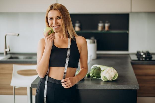 Mulher jovem com fita métrica na cozinha Foto gratuita