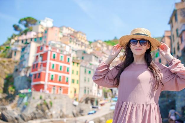 Mulher jovem, com, grande vista, em, antigas, vila, riomaggiore, cinque terre, liguria Foto Premium