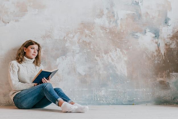 Mulher jovem, com, livro, perto, parede Foto gratuita