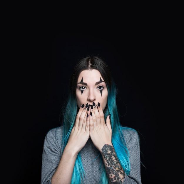 Mulher jovem, com, longo, cabelo azul, encerramento, boca, com, mãos Foto gratuita