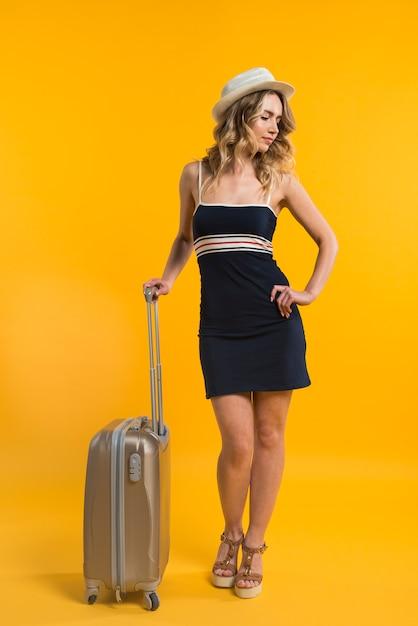 Mulher jovem, com, mala, esperando, para, vôo Foto gratuita
