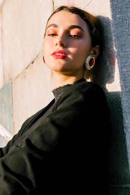 Mulher jovem, com, maquiagem, desgastar, brincos vermelhos, olhando câmera Foto gratuita