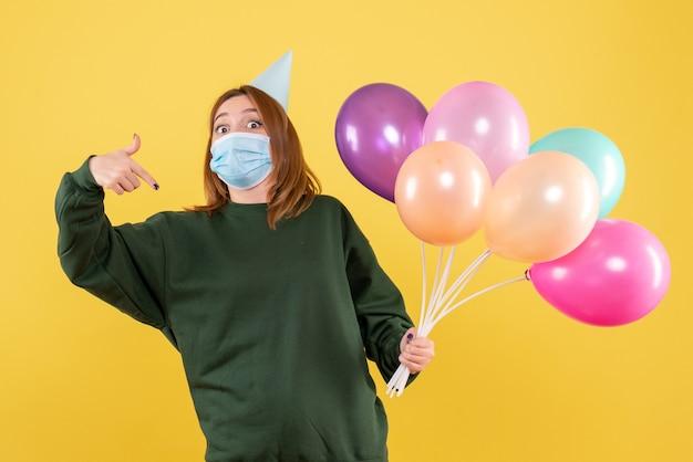 Mulher jovem com máscara segurando balões coloridos de frente Foto gratuita