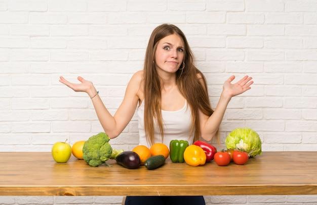 Mulher jovem, com, muitos, legumes, tendo, dúvidas, com, confunda, expressão expressão Foto Premium
