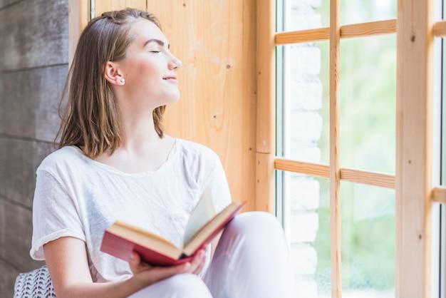 Mulher jovem, com, olho fechado, segurando, livro, relaxante, perto, a, janela Foto gratuita