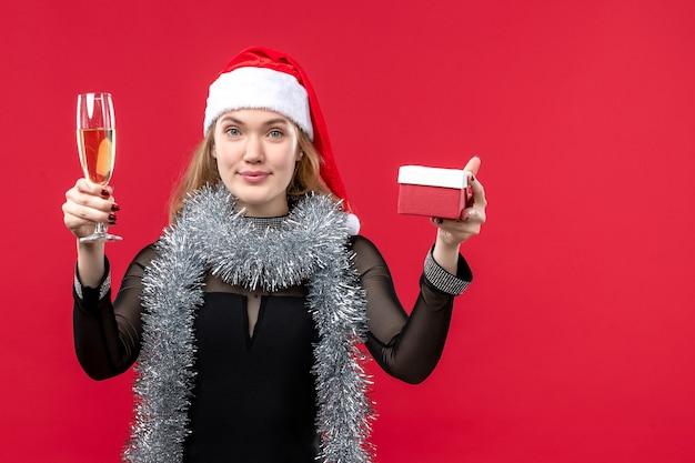 Mulher jovem com presente comemorando na parede vermelha feriado cor natal Foto gratuita