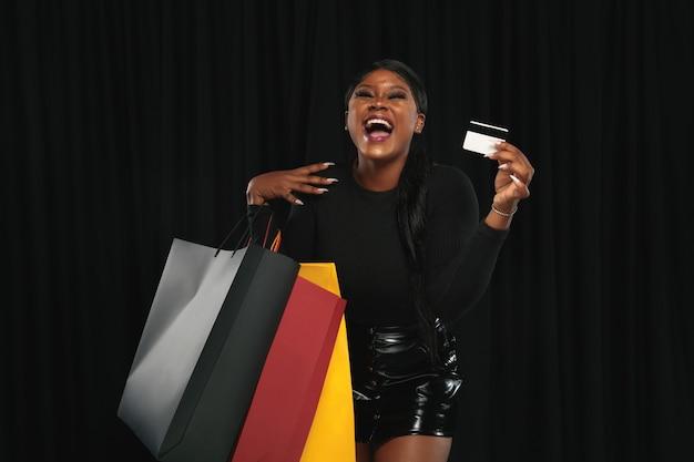 Mulher jovem com sacolas de compras e cartão de crédito Foto gratuita