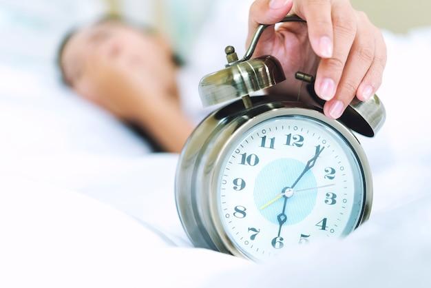Mulher jovem com sono na cama com os olhos fechados, estendendo a mão para o despertador Foto Premium