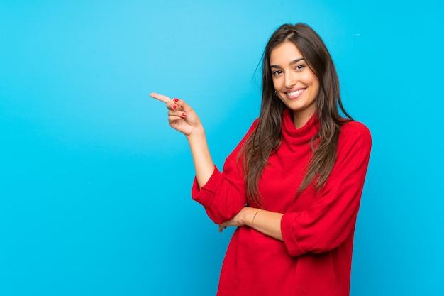 Mulher jovem, com, suéter vermelho, isolado, azul, apontando dedo, ao lado Foto Premium