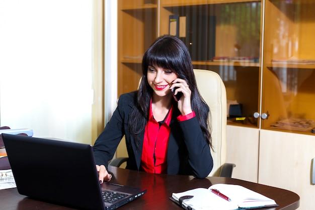 Mulher jovem, com, um, telefone móvel, sentando escrivaninha, em, escritório Foto Premium