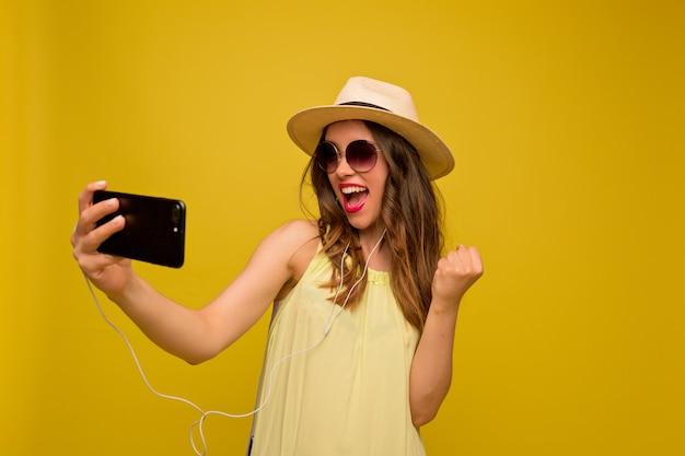 Mulher jovem com um vestido amarelo, chapéu e óculos escuros, assistindo ao vídeo Foto gratuita