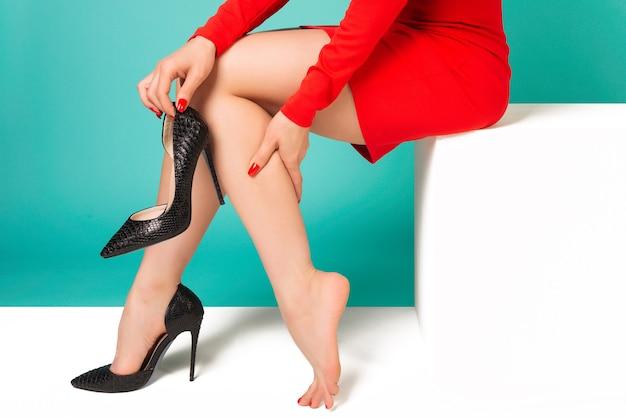 Mulher jovem com um vestido vermelho sofrendo de dores nas pernas no escritório por causa de sapatos desconfortáveis - imagem Foto Premium