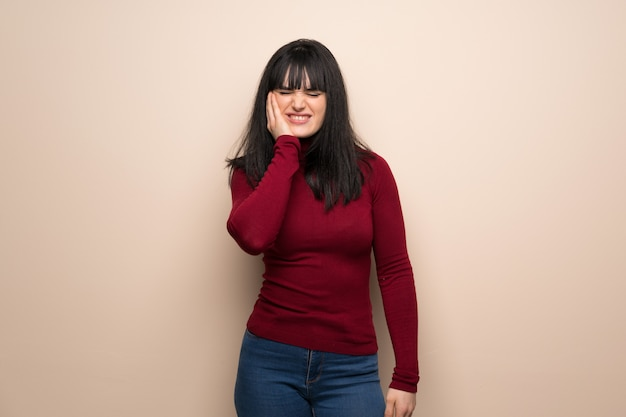 Mulher jovem, com, vermelho, gola alta, com, toothache Foto Premium