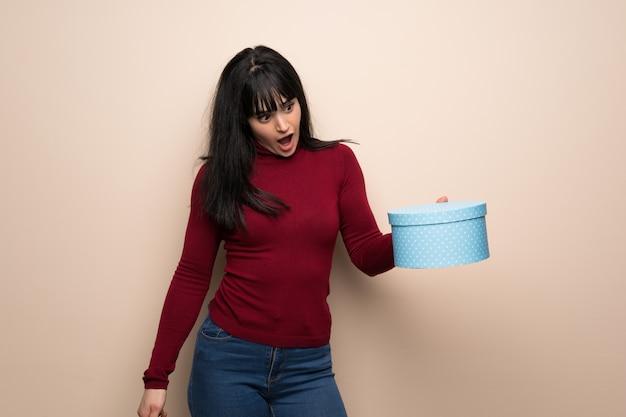 Mulher jovem, com, vermelho, gola alta, segurando, caixa presente, em, mãos Foto Premium