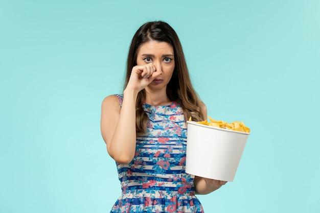 Mulher jovem comendo cips e assistindo filme chorando na superfície azul Foto gratuita