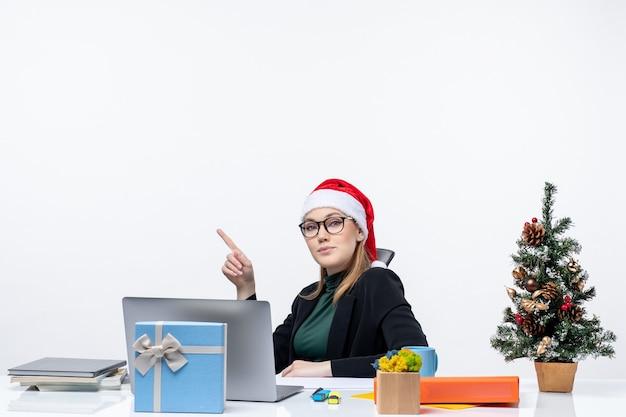 Mulher jovem confiante com chapéu de papai noel e óculos, sentada à mesa com uma árvore de natal e um presente nela. Foto gratuita