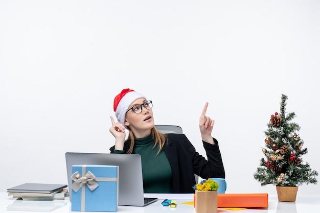 Mulher jovem confiante com chapéu de papai noel sentada a uma mesa com uma árvore de natal e um presente e apontando para cima no lado esquerdo em fundo branco Foto gratuita