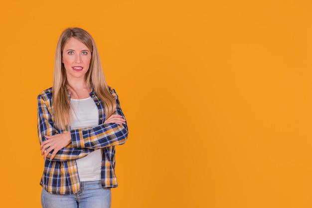 Mulher jovem confiante com o braço cruzado olhando para a câmera Foto gratuita