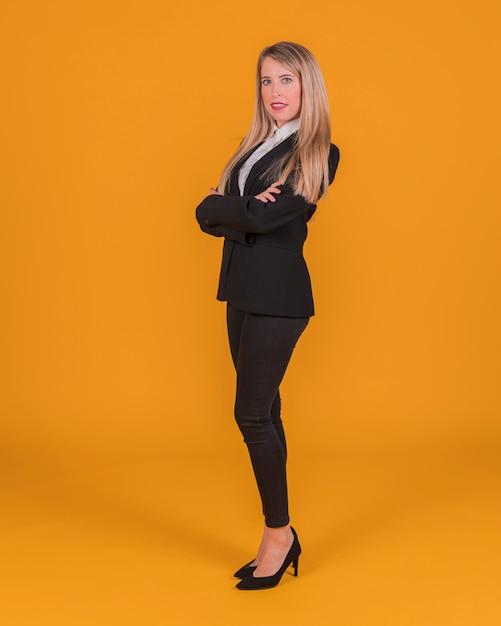 Mulher jovem confiante em pé contra um pano de fundo laranja Foto gratuita