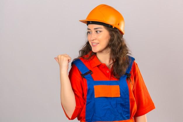 Mulher jovem construtor em uniforme de construção e capacete de segurança, sorrindo com cara feliz olhando e apontando para o lado com o polegar para cima sobre parede branca isolada Foto gratuita