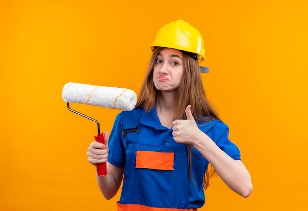 Mulher jovem construtora com uniforme de construção e capacete de segurança segurando o rolo de pintura mostrando os polegares em pé sobre a parede laranja Foto gratuita