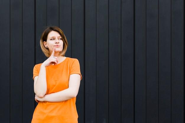Mulher jovem contemplada com o dedo no queixo contra parede preta Foto gratuita
