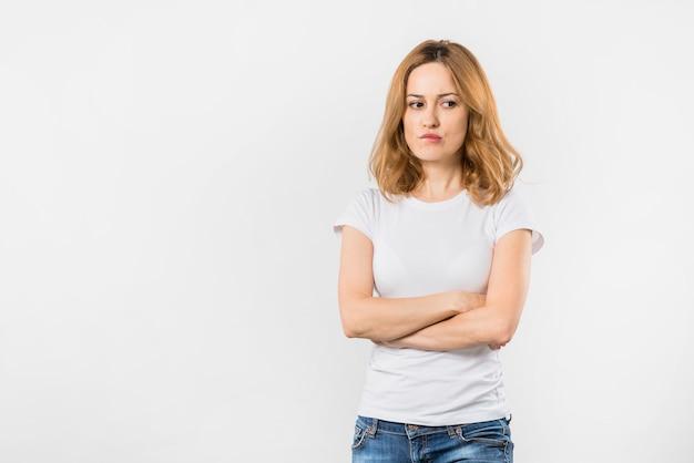 Mulher jovem contemplada franzindo os lábios em pé com os braços cruzados contra o pano de fundo branco Foto gratuita