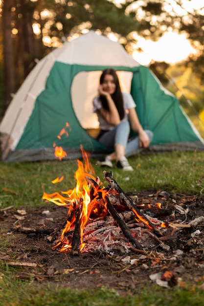 Mulher jovem curtindo uma fogueira na natureza Foto gratuita