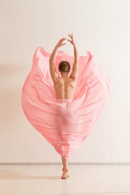 Mulher jovem dançando com um lindo vestido rosa Foto Premium