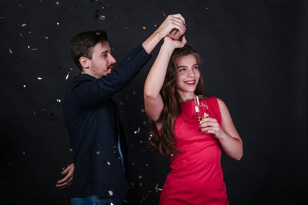 Mulher jovem, dançar, com, homem, com, vidro, de, bebida, entre, lançar confetti Foto gratuita