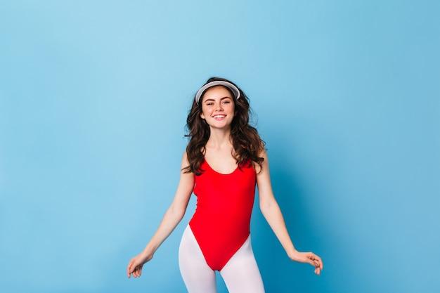 Mulher jovem de bochechas rosadas em um macacão vermelho e legging esportiva com um sorriso olhando para a frente na parede azul Foto gratuita