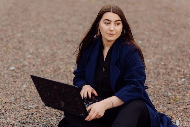 Mulher jovem de cabelos castanhos com laptop e computador telefone inteligente sentado sobre uma pedras Foto gratuita